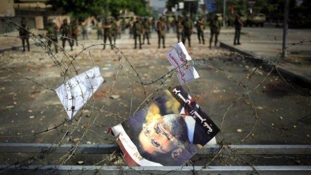 Tampak poster Mursi tersangkut di kawat berduri dengan latar belakang beberapa tentara berjaga.